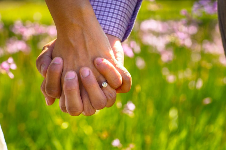 Close-up of couple's hands, showcasing the woman's engagement ring before their Laguna Beach engagement session