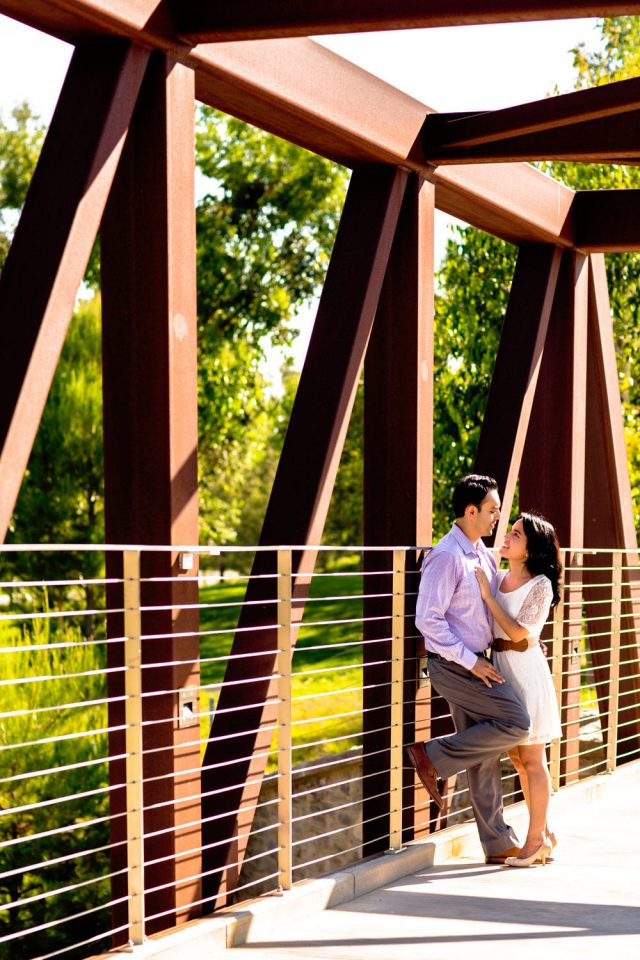 Couple talking with each other on a bridge in Jeffrey Open Space Trails before their Laguna Beach engagement session
