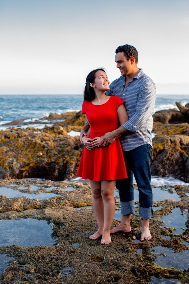 Man holding fiancee at Victoria Beach as part of their Laguna Beach engagement session