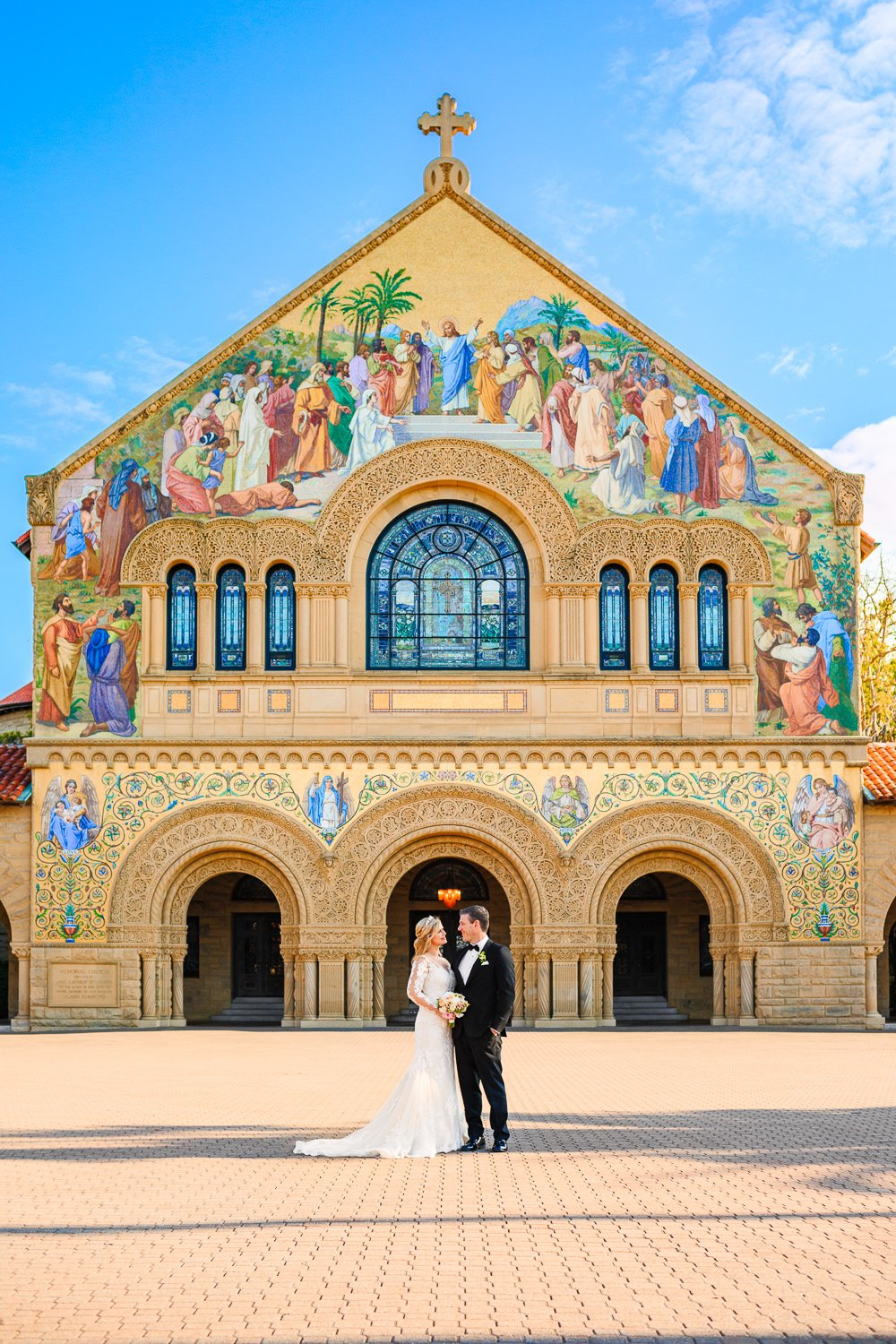 Bride and groom in front of chapel on campus at Stanford University